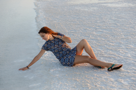 Calm girl enjoying sun, sits on the ground covered with salt close to lake