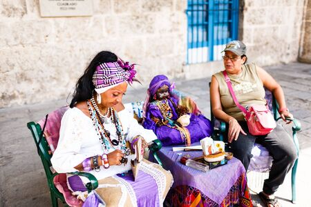 Dark-skinned Cuban in white costume tells fortunes to tourists in Havana streets
