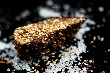 Luxury handmade dark chocolate with seasame and sea salt, black background