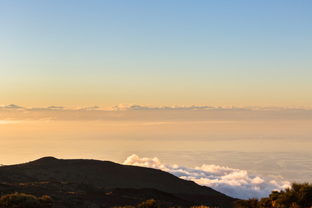 Clouds lie on the mountainside, calm ocean on the background 写真素材 - 121182748