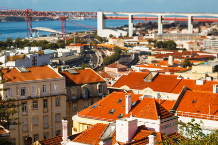 many bright tiled roofs of Lisbon, 25 th April Bridge connecting to of Almada 写真素材 - 121182755