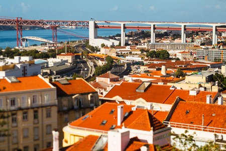 many bright tiled roofs of Lisbon, 25 th April Bridge connecting to of Almada 写真素材
