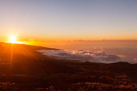 Incredible sunset landscape in the mountains. Clouds lie on the mountainside