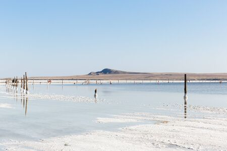 People on exotic beach of salt lake Baskunchak, view of Bogdo hill in Astrakhan