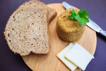 Serve beef pate with a piece of butter and bread on a wooden board, decorated with parsley 写真素材