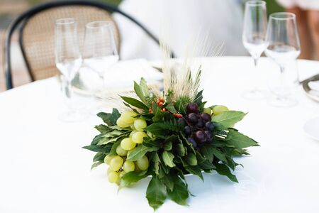Table setting for a romantic dinner in the summer outside. Unusual bouquet with bunches of grapes and laurel leaves 写真素材