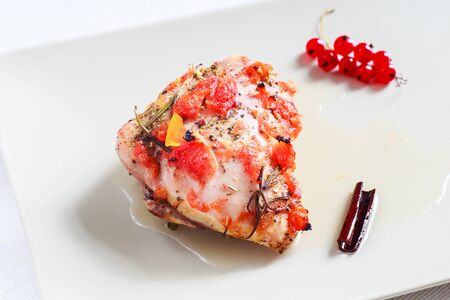 Baked chicken in grapefruit syrup with cinnamon and citrus fruit slices decorated with red currant Stok Fotoğraf