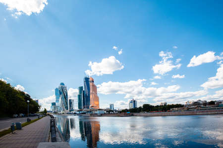 MOSCOW, RUSSIA - August, 05 2015: View of the international business center Moscow City from the Taras Shevchenko embankment. Tourists walking on the promenade. Summer sunny day