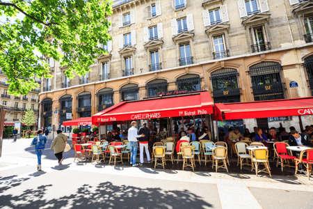 Paris, France - May 20, 2015: Parisians enjoy summer day drinks in cafe sidewalk, sunny spring day, red visor cafe, trees
