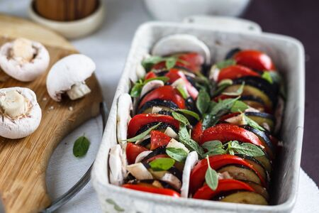 Parmigiano eggplant - a dish of Italian cuisine, vegetarian casserole with eggplant, basil, mushrooms, tomatoes and cheese