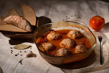 meatballs in tomato sauce in a glass dish, rye bread, linen tablecloth, Low key 写真素材