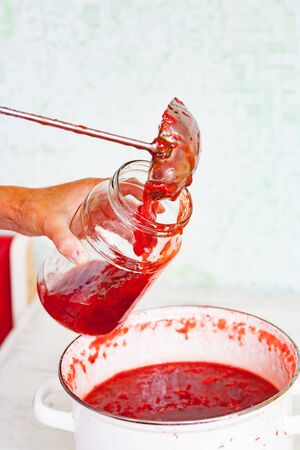 pour fresh strawberry jam into a jar with steel ladle