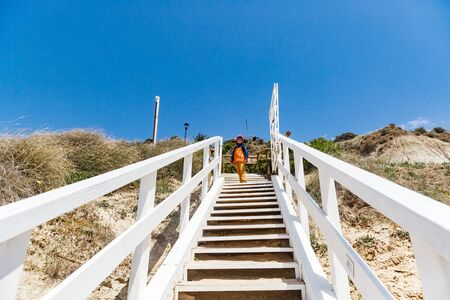 the seashore near the Scala dei Turchi in Sicilia. A cute boy in a windbreaker and sunglasses stands on top of a wooden white staircase on the windy coast. Clear blue sky