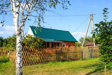 Beautiful summer country house with an emerald roof, a wooden fence around, a young birch and maple, a peaceful landscape 写真素材