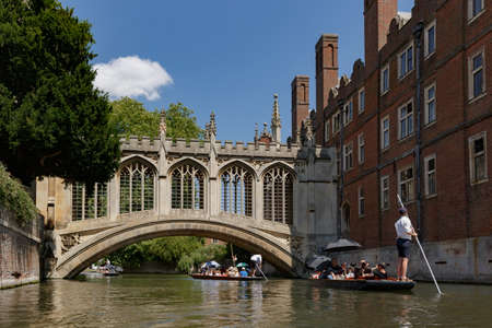 Cambridge, United Kingdom, July 23, 2019: On a sunny day guides take tourists on a chauffeured boating tour under the famous covered Bridge of Sighs at St John's College, Cambridge, United Kingdom