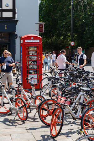 Cambridge, United Kingdom, July 23, 2019: Famous british Red phone booth and many bicycles near Cambridge Punters. Crowd of people, summer sunny day