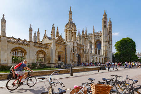 Cambridge, United Kingdom, July 23, 2019: Many tired people seat in shade near gothic King's College Porters' Lodge, many bikes near, lively evening street. Great St Mary's Church on background 報道画像