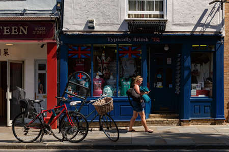 Cambridge, United Kingdom, July 23, 2019: woman walks past a gift shop and parked bicycles in the streets near Cambridge Punters. Summer sunny day 報道画像