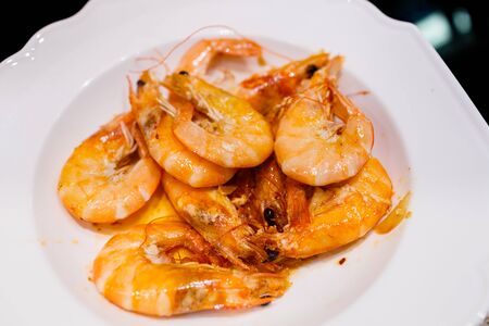 deep-sea shrimp fried in olive oil with garlic in a small frying pan on an induction electric panel 写真素材
