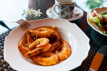 delicious lunch of fried shrimp in olive oil with garlic, green salad and a cup of coffee, black table