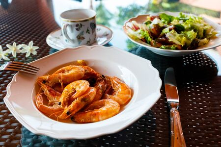 delicious lunch of fried shrimp in olive oil with garlic, green salad and a cup of coffee, black table, flat lay