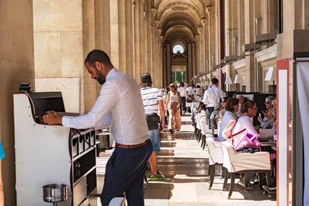 Parisians and tourists enjoy summer day drinks in cafe on a terrace of Louvre