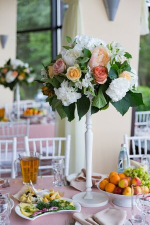 Thin high decorative vase with lush bouquet on the table for the holiday dinner