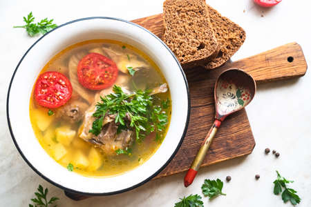 fish soup with carp, potatoes, parsley, tomato in enamel bowl stands on a board Stock Photo