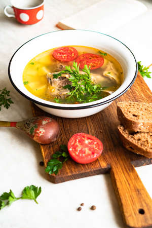 fish soup with carp, potatoes, parsley, tomato in enamel bowl stands on a board 写真素材