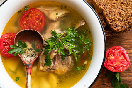 fish soup with carp, potatoes, parsley, tomato in enamel bowl stands on a board