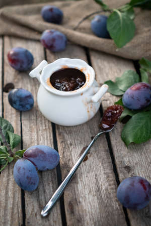 plum jam in a white ceramic pot on an aged wooden background, fresh plums near