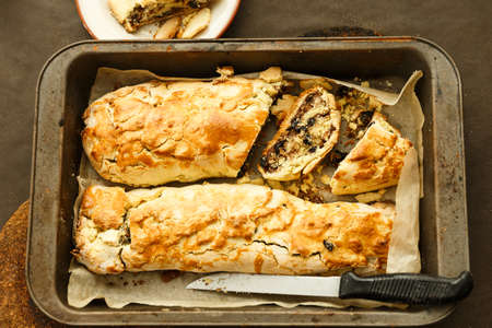 Two rolls with raisin and nuts on the pan and baking paper Banco de Imagens