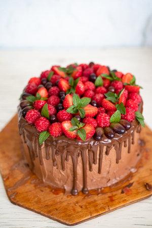 Homemade beautiful chocolate cake with raspberries, strawberries, mint, grapes
