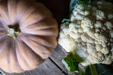 pumpkin and cauliflower on wooden background, close up still life