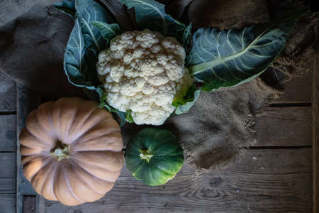 pumpkin and cauliflower on wooden background, close up still life with burlap Banco de Imagens