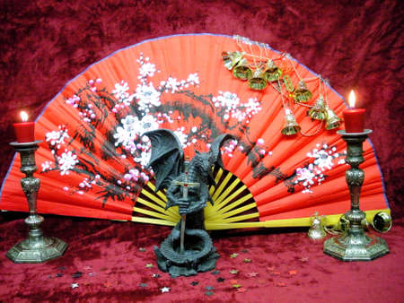 Chinese fan , dragon with sword and red candles.