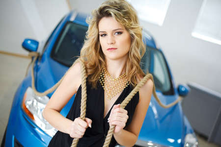Young woman in the showroom with a new car with ropes on their shoulders photo