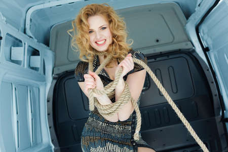 Pretty young woman in ropes in cargo van inside  photo