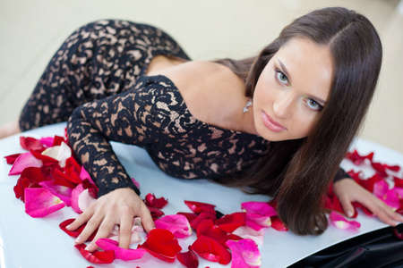 Young pretty woman with a New car in red rose petals  photo