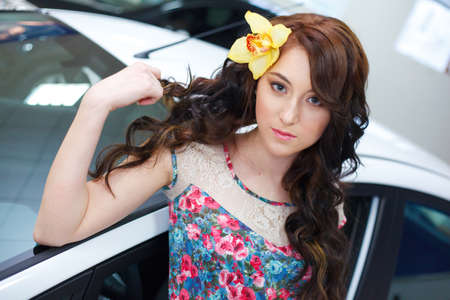 Young pretty woman with a New car photo