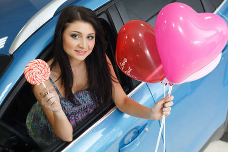 Young woman with candy and heart baloons with New car photo