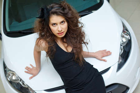 Young woman on white hood of New car photo