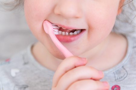 Cute little child in bathroom cleaning the teeth with pink brush. 免版税图像