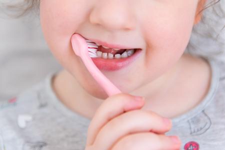 Nettes kleines Kind im Badezimmer, das die Zähne mit rosa Bürste säubert Standard-Bild