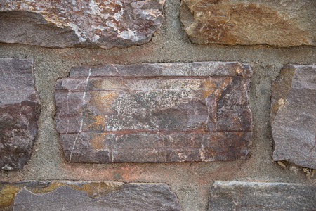 Textural stone wall from an old brick of the architectural building.
