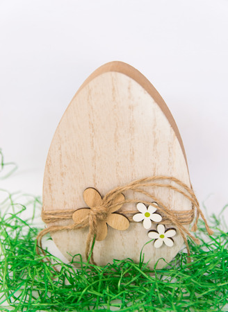 Easter wood handmade egg with green spring grass on the beige background. Easter concept.