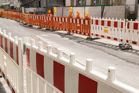 Repair work on the street. Orange and white barrier for security and traffic. Building construction concept.