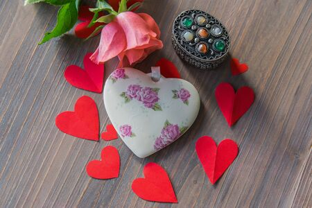 Porcelain heart with flowers on the wood textural table with pink flower and many red paper hearts around. Wedding or love sign. Flat lay.