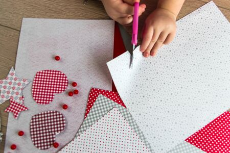 The hand of the child make greeting card with heart. Decoration on the background. Hobby concept. Handmade. Childrens DIY concept.