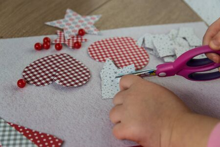 The hand of the child make greeting card with heart. Hobby concept. Handmade.